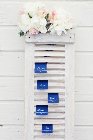 Nautical Seaside Wedding Inspiration seating chart idea with blue handwritten escort cards