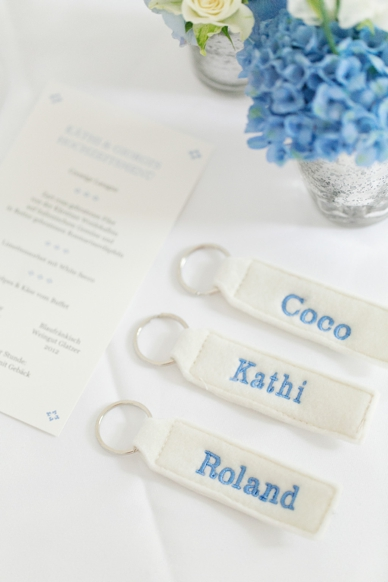 Cutest giveways - keychaines with names of the guest, light blue and white table decoration at this delicate lakeside wedding, photography by peaches & mint, best Austrian wedding photographers