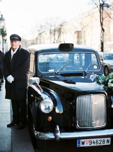 Oldtimer bridal car and driver in front of Kempinski Vienna