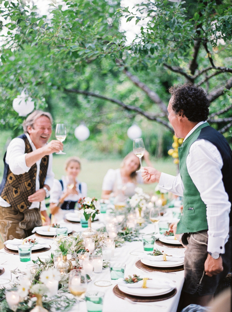 Raise your glasses and toast at a summer wedding in Austria destination wedding photography by peachesandmint.com