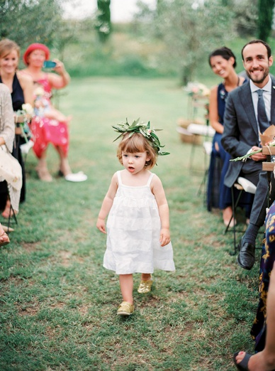 cutest ever flower girl with olive wreath at Tuscany destination wedding amidst the olive grove