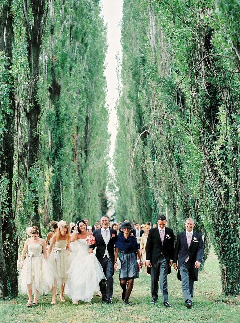The epic tree-lined alley walk from the chapel to the Villa Gallici Deciani in Italy wedding photography by peachesandmint.com